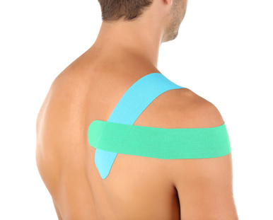 Physio tape on shoulder of sporty man isolated on white